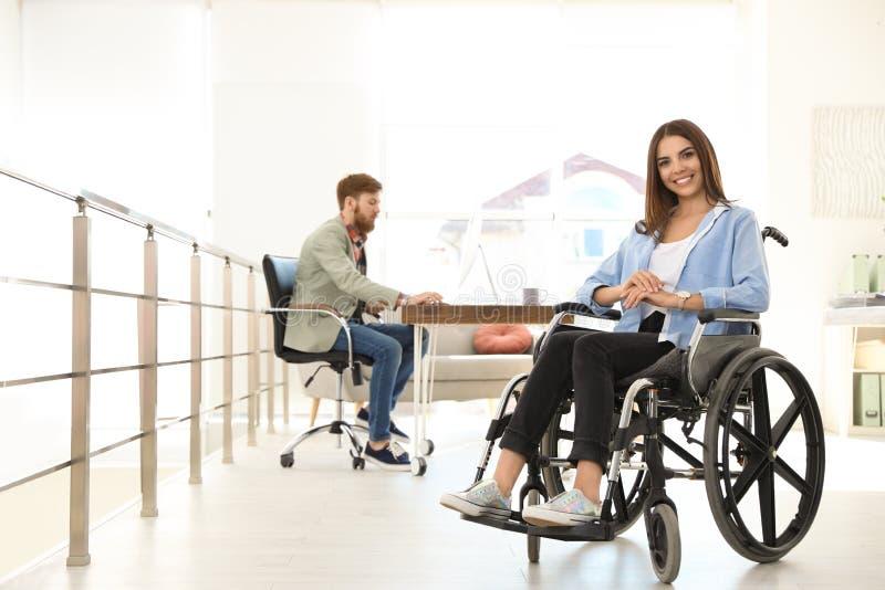 Ung kvinna i rullstol med kollegan p? kontoret arkivbild