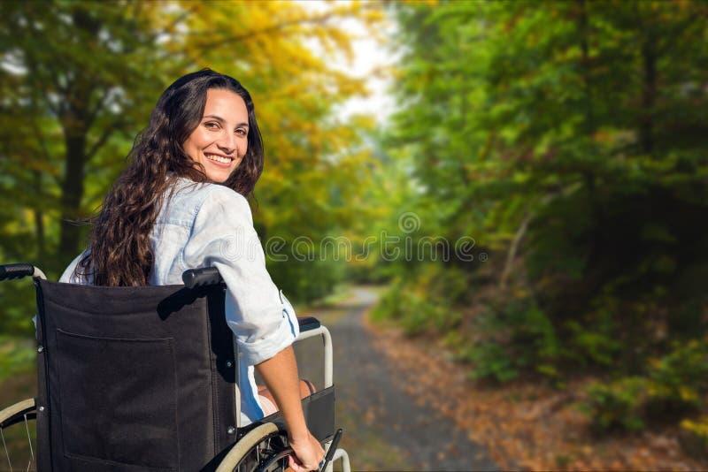 Ung kvinna i rullstol på gatan arkivfoton