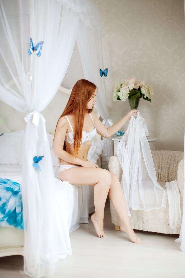 Ung kvinna i säng i morgonen royaltyfri fotografi