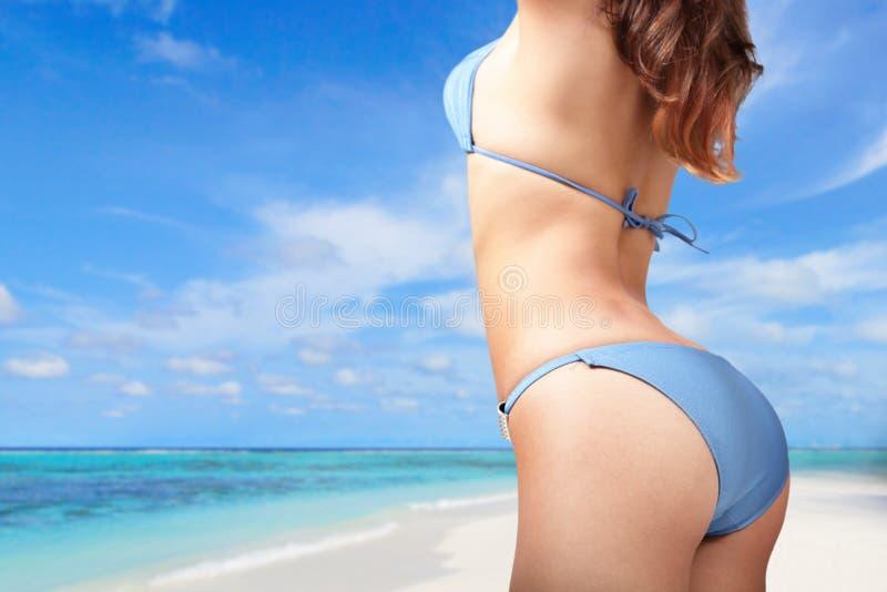 Ung kvinna i sexig bikini på stranden arkivbild