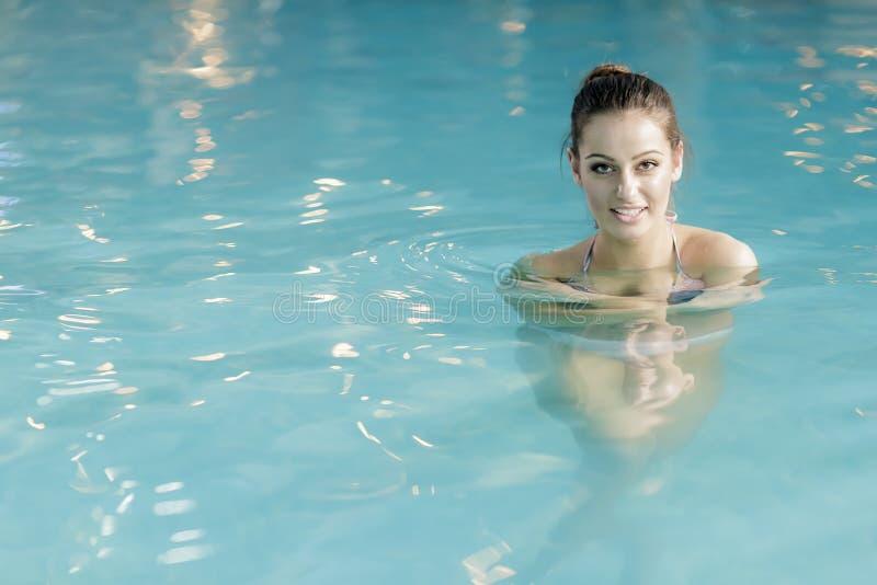 Ung kvinna i simbassängen arkivbild