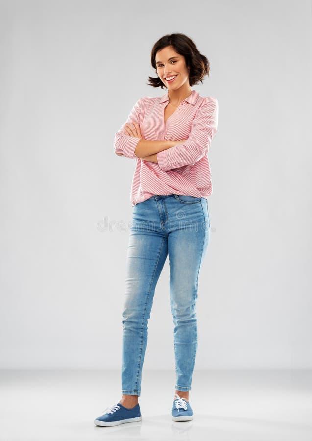 Ung kvinna i skjorta och jeans med korsade armar arkivbild
