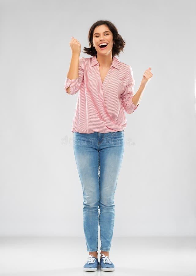 Ung kvinna i skjorta och jeans som firar framgång arkivfoton