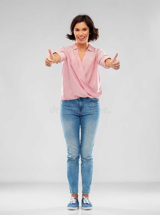 Ung kvinna i skjortan och jeans som visar upp tummar royaltyfria foton