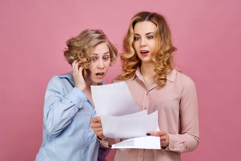 Ung kvinna i skjortan som mycket är förvånad vid erhållande resultat och i chockblick på dokument som talar medan på telefonen arkivfoton
