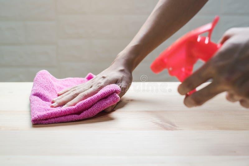 Ung kvinna i skyddande handskar genom att anv?nda en dammtrasa och en sprej royaltyfri fotografi