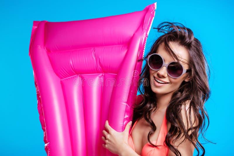 Ung kvinna, i solglasögon och hållande luftmadrass för bikini och att le på kameran royaltyfri bild