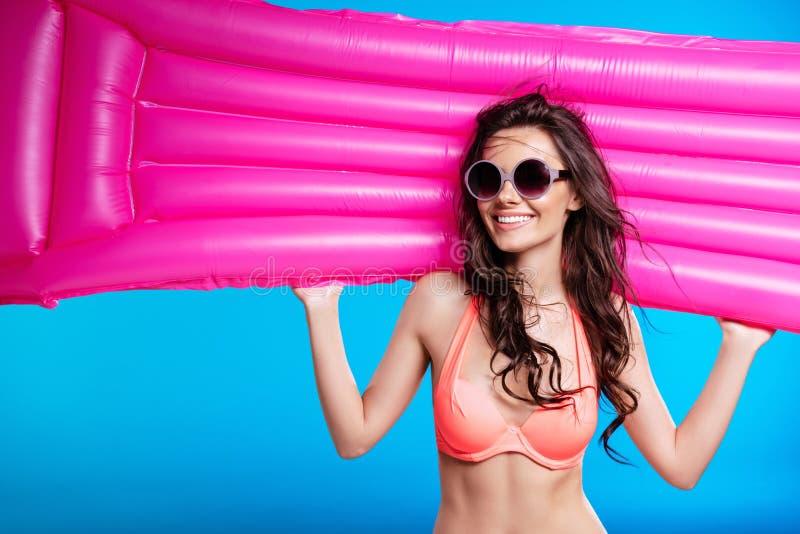 Ung kvinna, i solglasögon och madrass och att le för simning för baddräkt hållande royaltyfria bilder