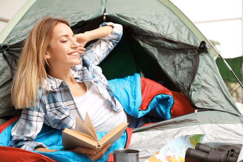 Ung kvinna i sovsäckläsebok utanför royaltyfri bild