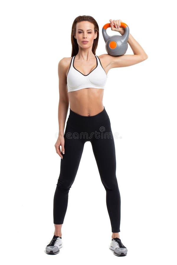 Ung kvinna i sportswearen som rymmer kettlebell isolerad royaltyfri foto
