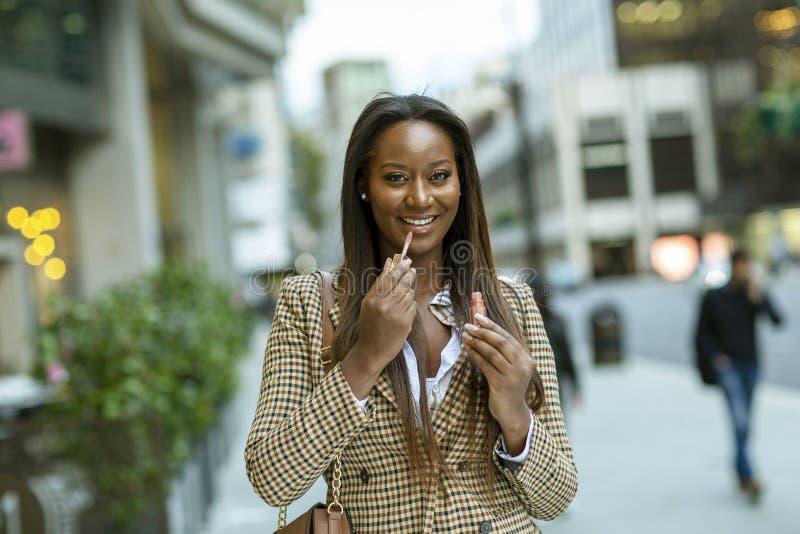 Ung kvinna i staden som sätter på lipsgloss royaltyfria bilder