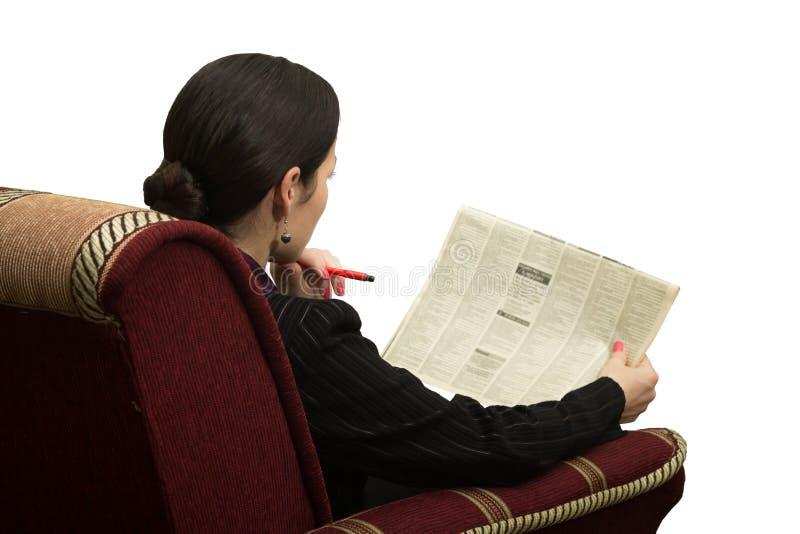 Ung kvinna i stol som l?ser en tidning med en annonsering royaltyfri foto