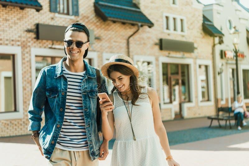 Ung kvinna i sugrörhatt genom att använda smartphonen, medan stå nära den utomhus- stiliga pojkvännen royaltyfria foton