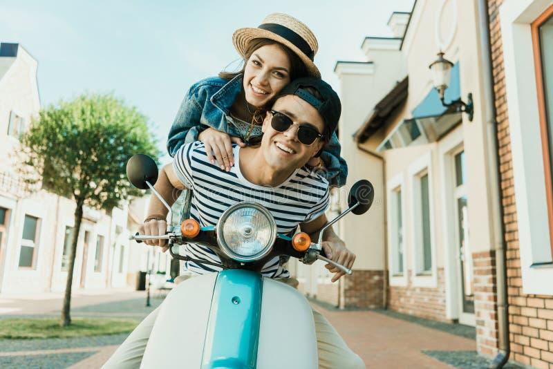 Ung kvinna i sugrörhatten och den stiliga mannen i sunglases som tillsammans rider sparkcykeln arkivbilder