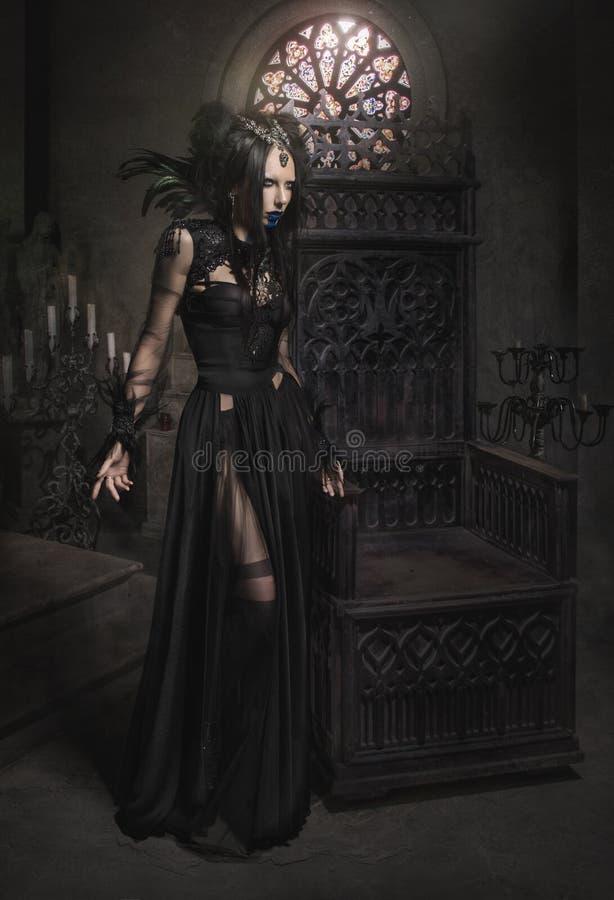 Ung kvinna i svart fantasidräkt med fjädrar royaltyfri fotografi