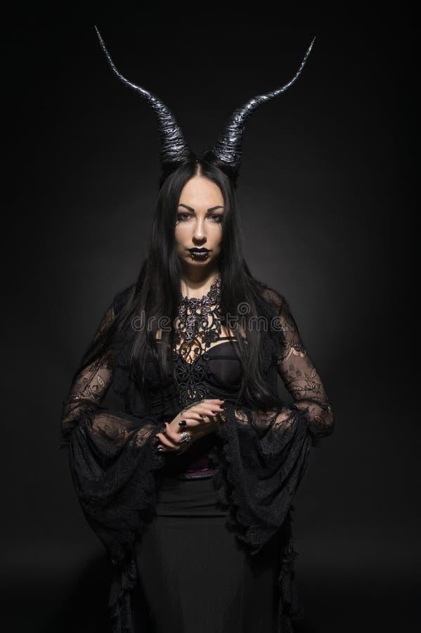 Ung kvinna i svart fantasidräkt med stora horn arkivfoto