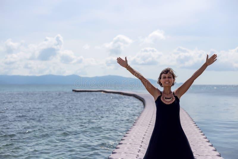 Ung kvinna i svart klänning på pir i havet royaltyfri fotografi