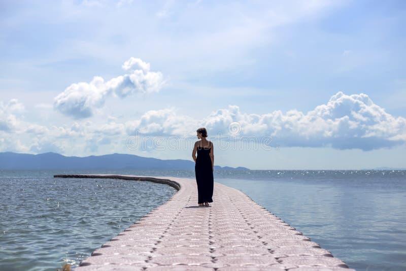 Ung kvinna i svart klänning på pir i havet arkivfoto