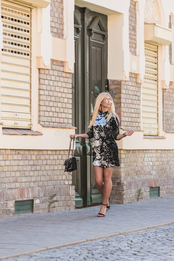 Ung kvinna i svart klänning som går på stadsgatan arkivfoto
