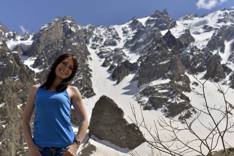 Ung kvinna i t-skjorta bland snöig berg royaltyfri fotografi