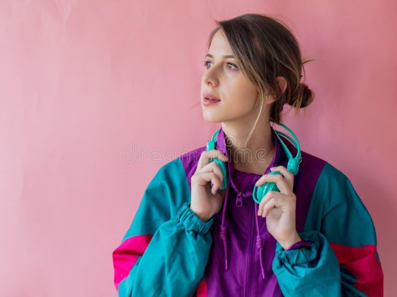 Ung kvinna i 90-talstilkläder med hörlurar fotografering för bildbyråer