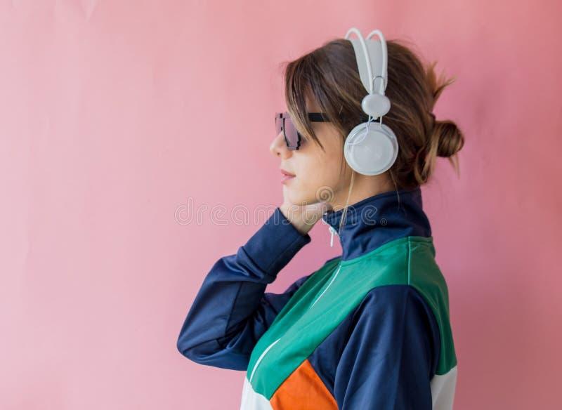 Ung kvinna i 90-talstilkläder med hörlurar royaltyfria foton