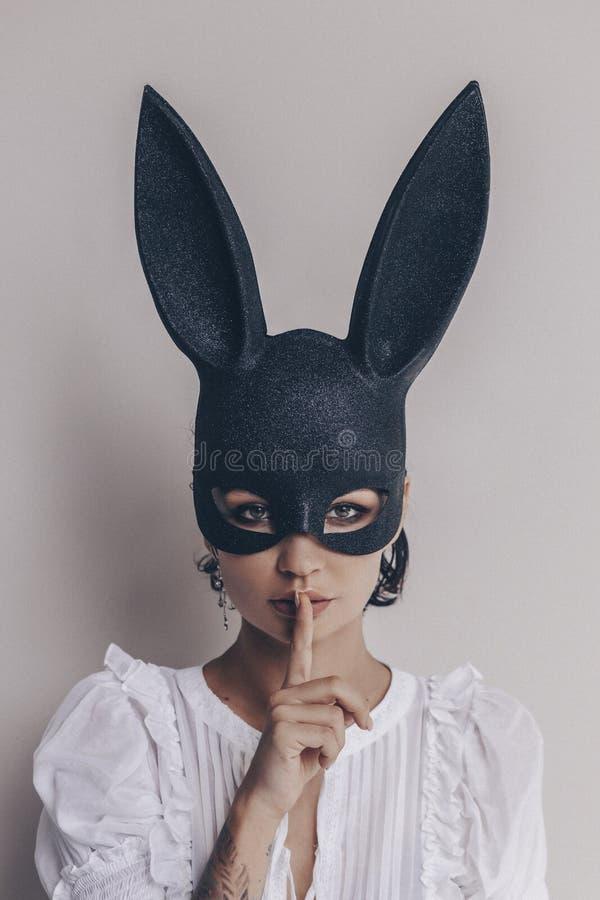 Ung kvinna i tecken för tystnad för kaninmaskeringsvisning royaltyfria foton
