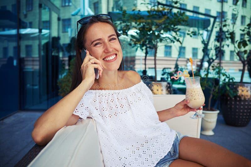 Ung kvinna i tillfällig kläder med coctailen som talar på telefonen arkivfoto