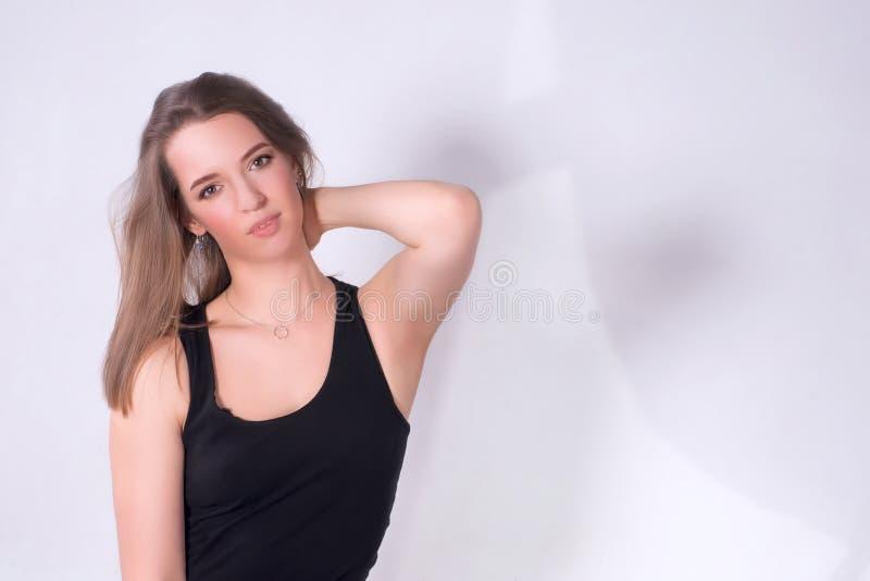 Ung kvinna i tillfälligt mot den vita väggen med ljusa skuggor fotografering för bildbyråer