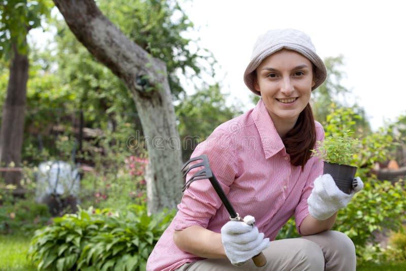 Ung kvinna i trädgården royaltyfri foto
