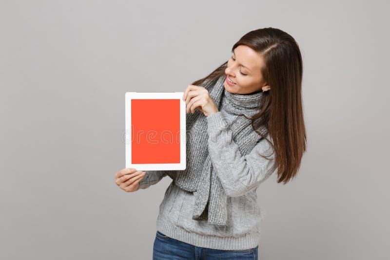 Ung kvinna i tröjan, halsduk som ser på minnestavlaPCdatoren med den tomma tomma skärmen som isoleras på grå bakgrund Sunt royaltyfria foton