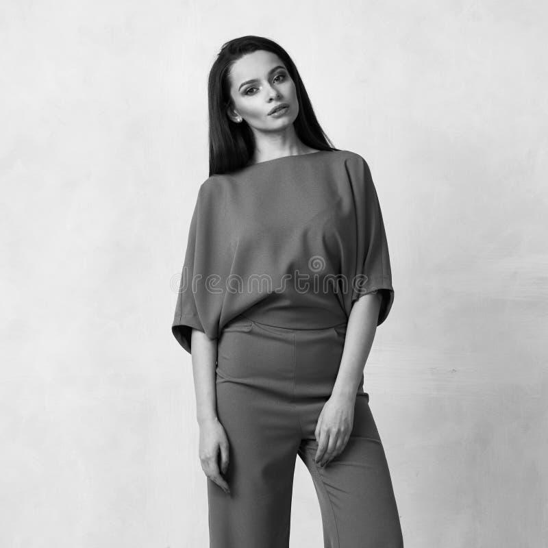 Ung kvinna i trendig malvafärgad jumpsuit fotografering för bildbyråer