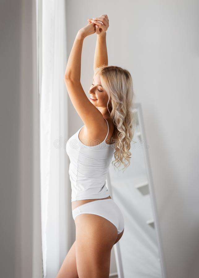 Ung kvinna i underkläderna som sträcker det hemmastadda fönstret arkivbilder