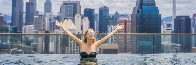 Ung kvinna i utomhus- simbass?ng med stadssikt i bl? himmel De rika BANER, LÅNGT FORMATBANER, LÅNGT FORMAT royaltyfria foton