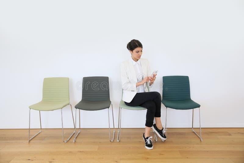 Ung kvinna i väntande rum genom att använda smartphonen royaltyfria bilder