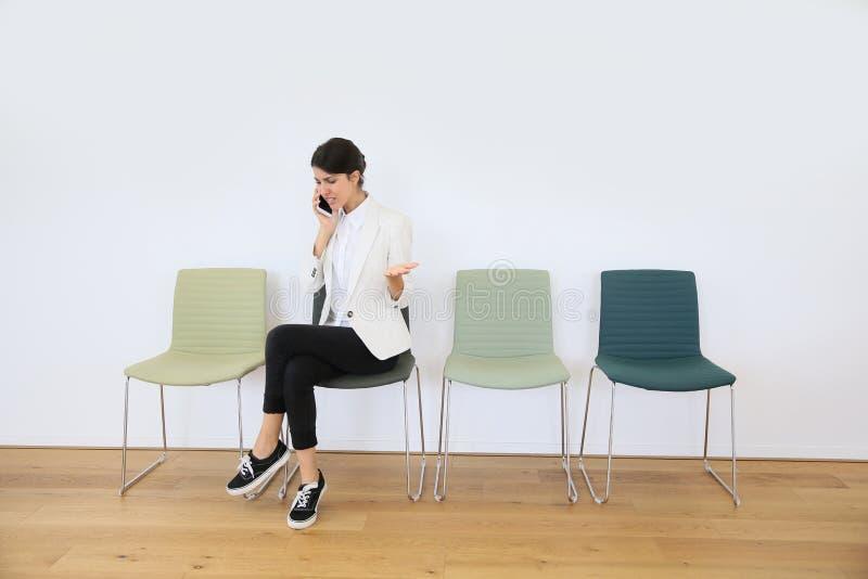 Ung kvinna i väntande rum som talar på telefonen arkivfoto
