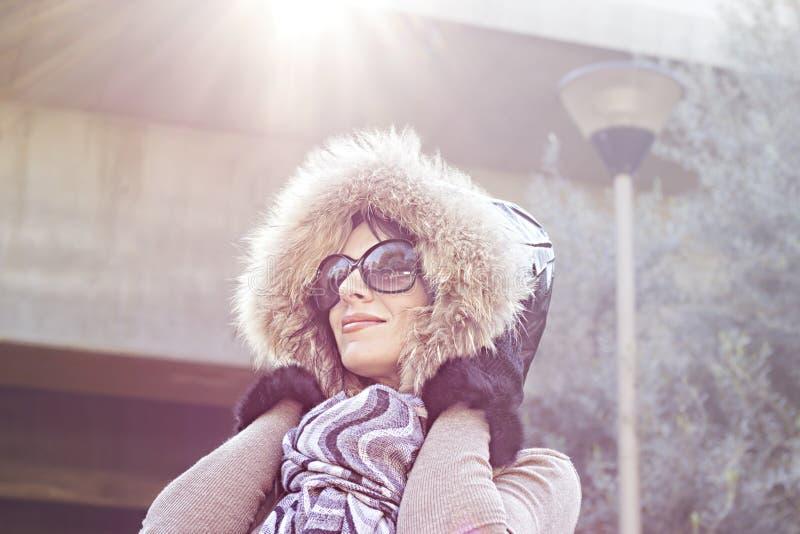 Ung kvinna i varm huv på head utomhus- tyckande om solljus på solig dag royaltyfria bilder