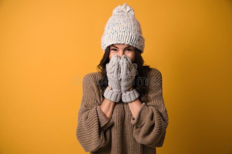 Ung kvinna i varma tröja, hatt och tumvanten på bakgrund Juls?song arkivfoto