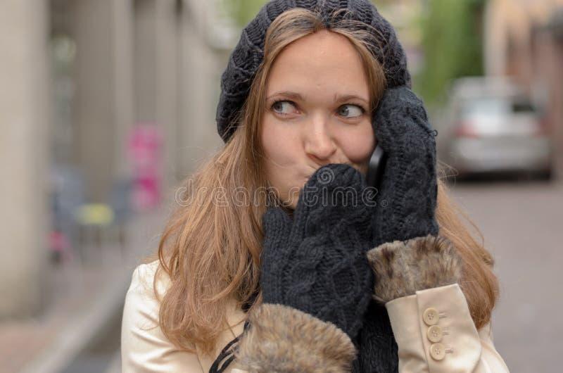 Ung kvinna i vintermode som kallar på telefonen arkivbilder