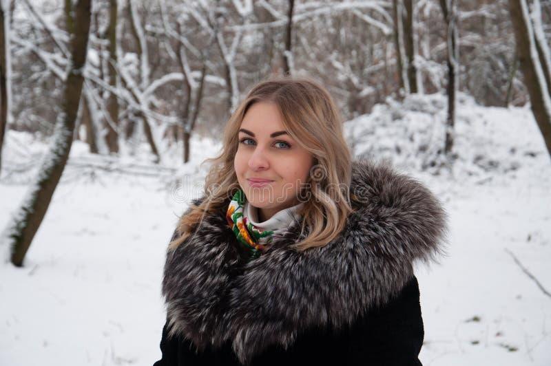 Ung kvinna i vinterstående Flickan i vintern parkerar fotografering för bildbyråer
