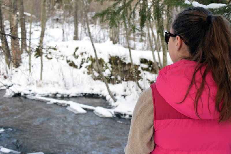 Ung kvinna i vintrig skog arkivbild