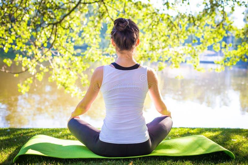 Ung kvinna i vit bästa praktiserande yoga i härlig natur arkivbilder