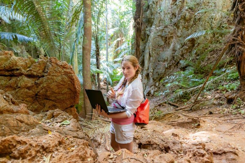 Ung kvinna i vita arbeten med en b?rbar dator i bergen och den tropiska djungeln Arbete i lopp Han ser in i kameran arkivfoto