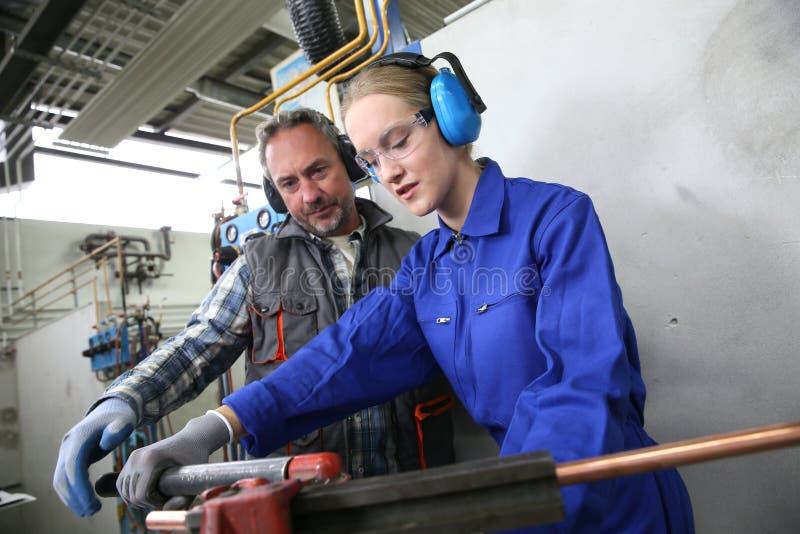 Ung kvinna i yrkesmässig plumberyutbildning arkivfoton