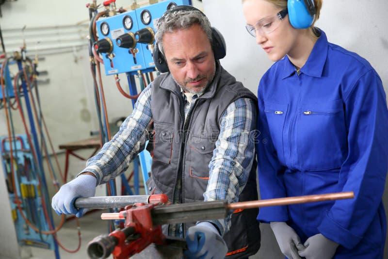 Ung kvinna i yrkesutbildning av plumberyen royaltyfri bild