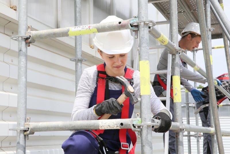 Ung kvinna i yrkesutbildningmaterial till byggnadsställning arkivfoton