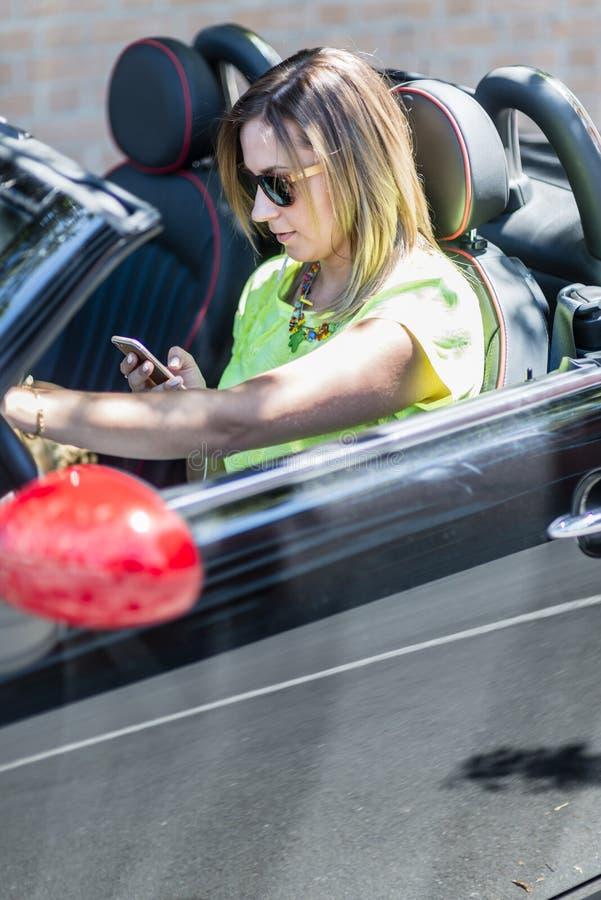Ung kvinna köra en cabrioletbil distraherat med hennes telefon arkivfoton