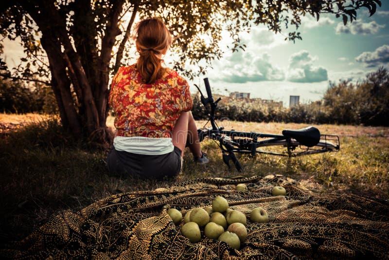 Ung kvinna med äpplen och cykeln arkivbild