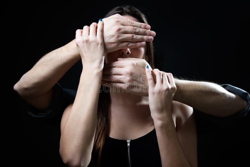 Ung kvinna med ögon och munnen som täckas av manliga händer Handlin royaltyfri bild