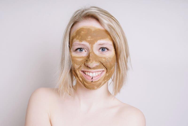 Ung kvinna med att läka den ansikts- maskeringen för jord- eller leraskönhet arkivbilder